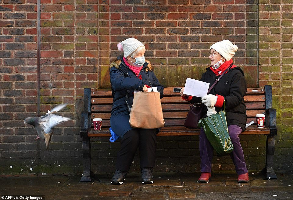 People wearing a face mask or covering due to the COVID-19 pandemic, sit and talk on a bench in York. The rules state only two people from different households can meet until April