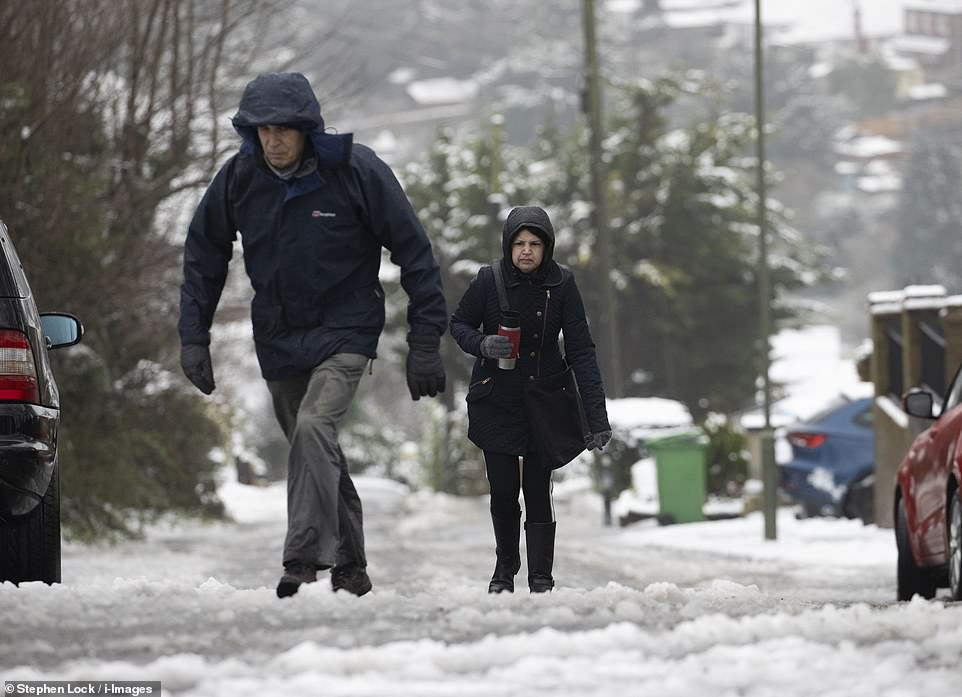 A couple trudge through the snow in Biggin Hill Kent this morning as people enjoyed their daily exercise