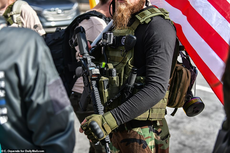 GEORGIA: An heavily armed protester is shown in the above image standing with a militia outside of Georgia's Capitol
