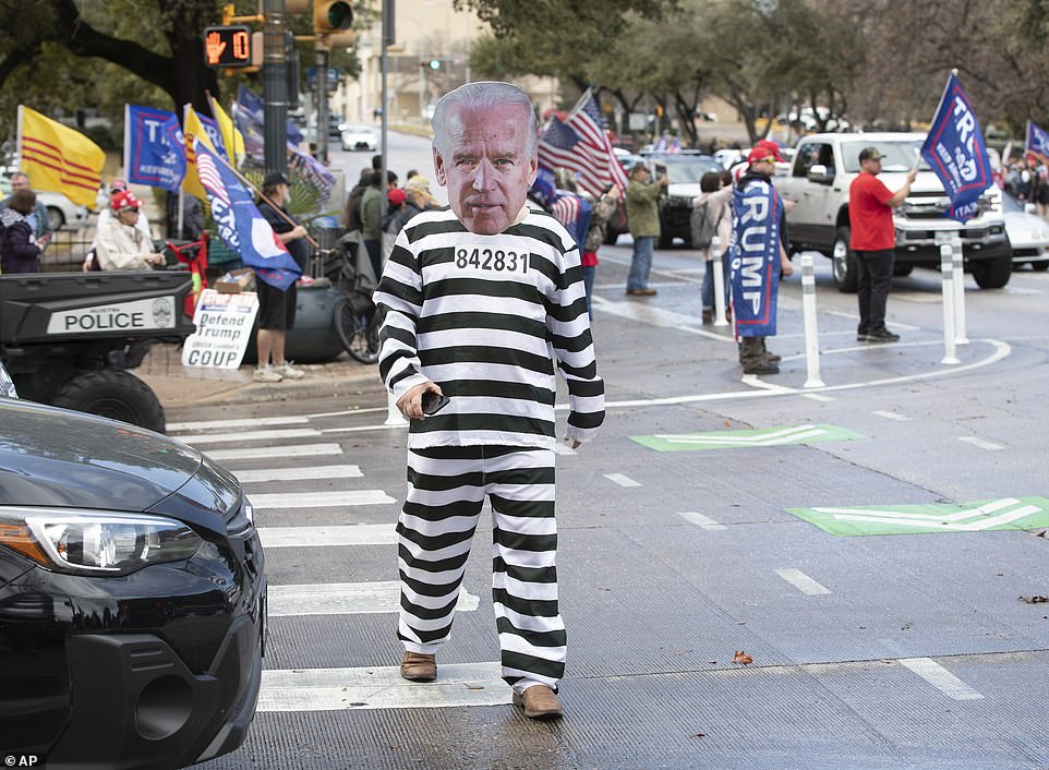 TEXAS: A Trump support is seen wearing a Biden mask with prison scrubs during a march in Austin on Wednesday