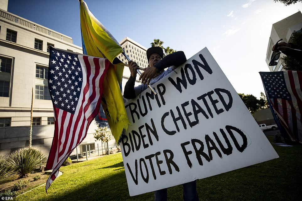 LA: A Trump supporter holds a placard reading 'Trump Won Biden Cheated Voter Fraud' during a demonstration outside City Hall