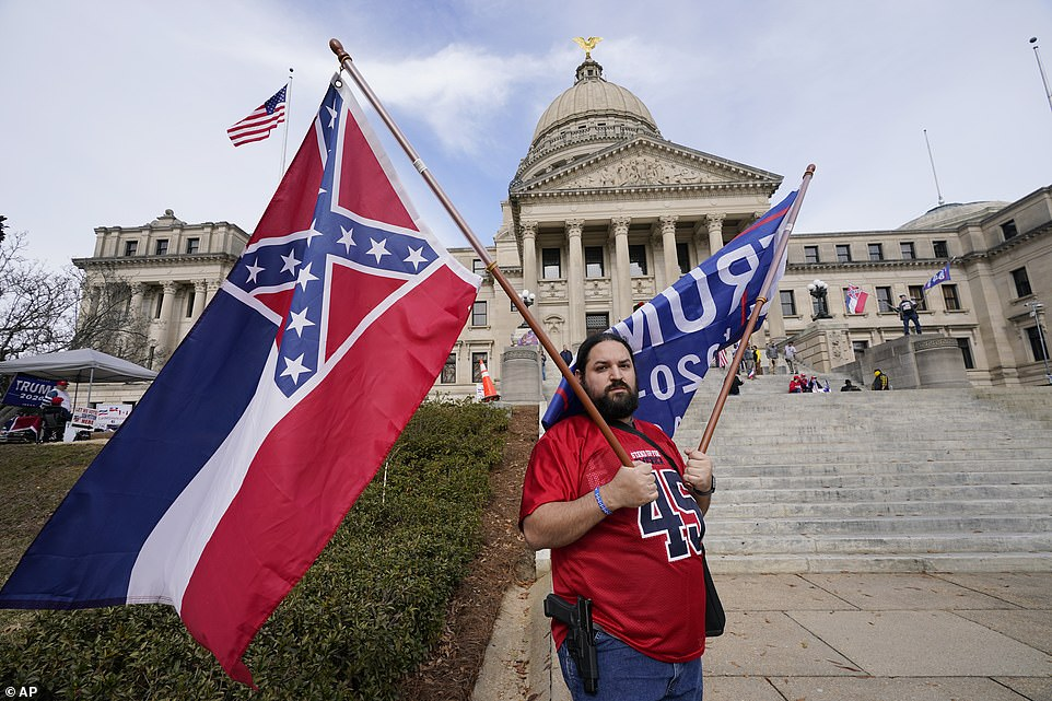 MISSISSIPPI: Jason Lavoie of Raymond, carries both the retired Mississippi state flag and a pro-Trump banner as he joined a small group of people that protested outside the Capitol in Jackson with a pistol on his hip