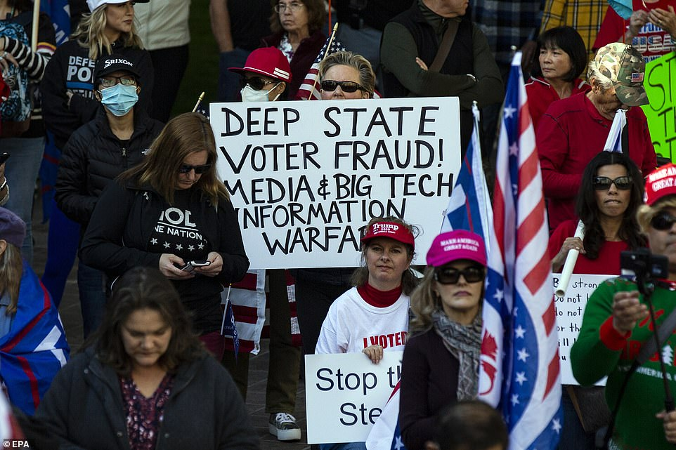 LA: A Trump supporter holds a placard reading 'Deep State Voter Fraud! Media and Big Tech Information Warfare'