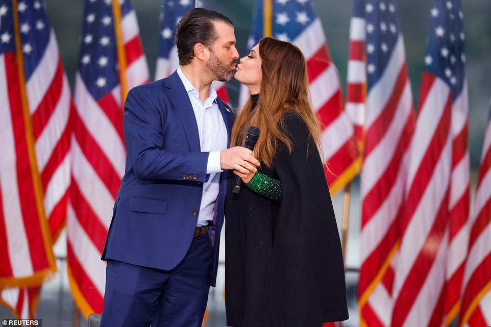 Donald Trump Jr (left), the president's eldest son, kisses his girlfriend, Kimberly Guilfoyle (right), before addressing the rally on Wednesday