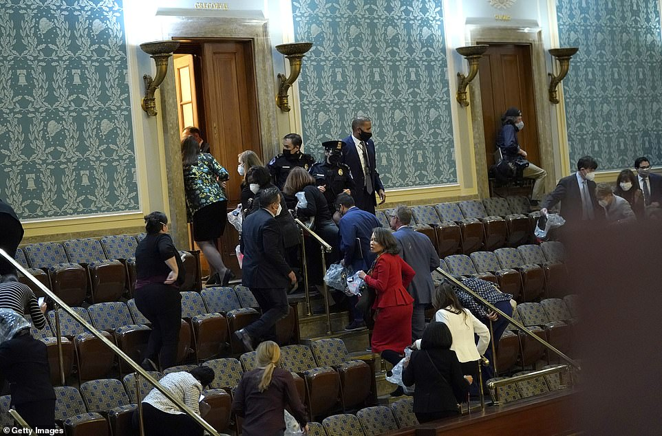 Members of Congress are pictured rushing to evacuate the House Chamber as protesters attempted to enter