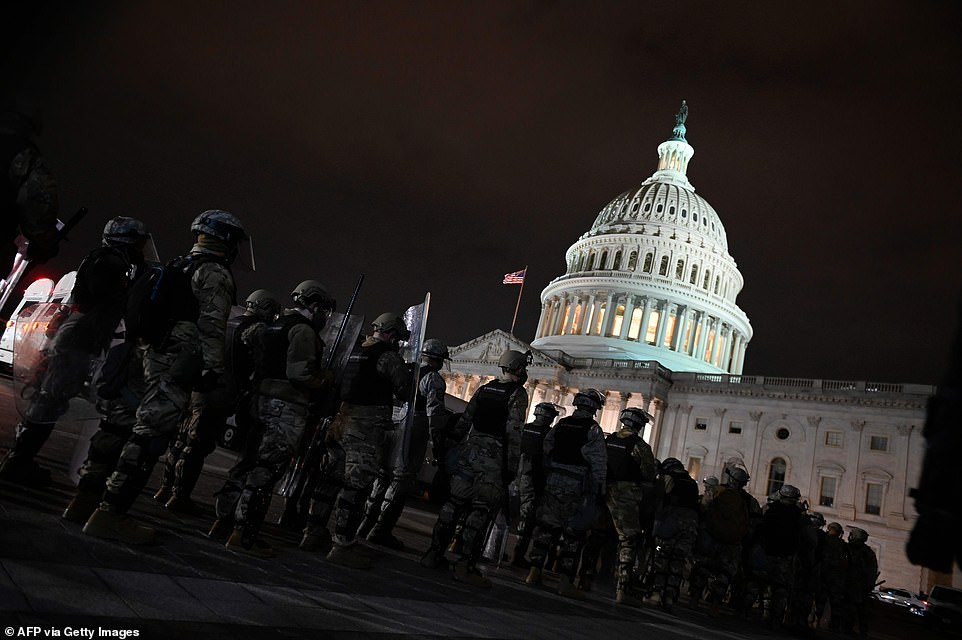 National Guard members line up on the Capitol grounds as protesters continue occupying the area after curfew