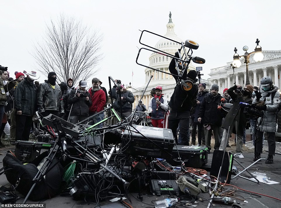 A vandal is seen destroying the equipment in ongoing scenes of chaos in Washington DC Wednesday