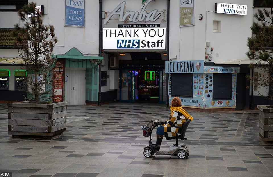 A person in a mobility scooter passes a 'Thank you NHS Staff' sign on the sea front on Bournemouth Beach in Dorset