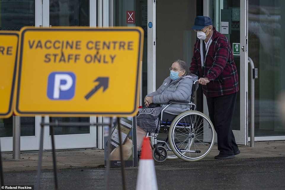 Two Britons arrive at the Covid-19 vaccine centre in Epsom Downs Racecourse, Surrey, today. The roll out is expected to ramp up in the coming weeks