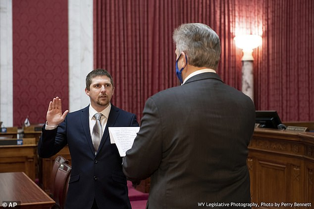 Evans is seen left on December 14th being sworn into the West Virginia House of Delegates, where he represents the 19th district encompassing Wayne County
