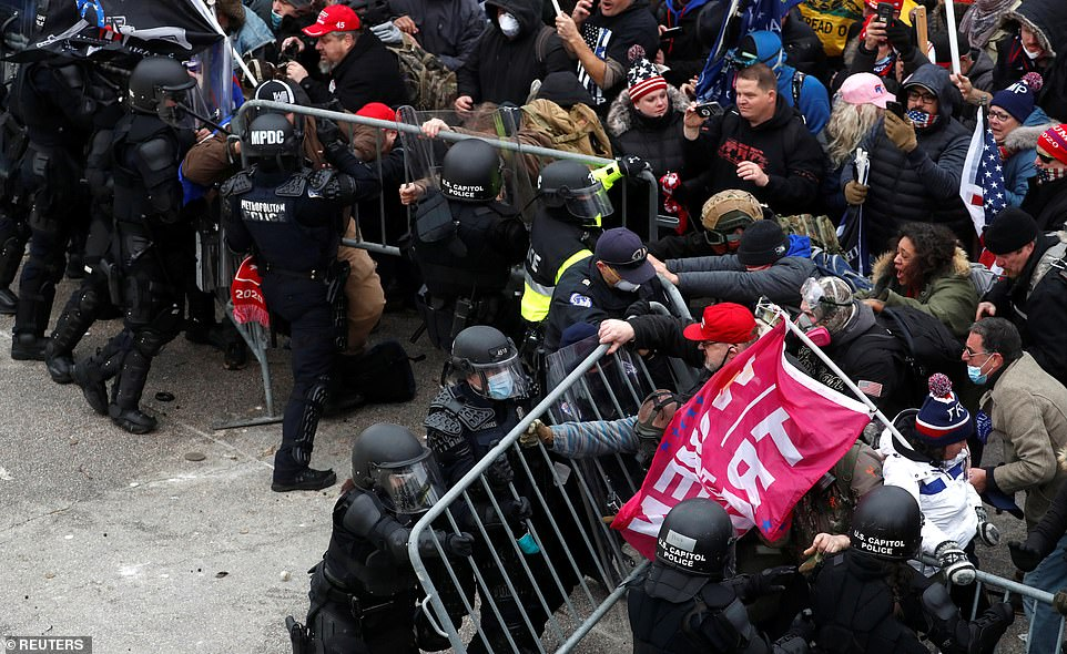 Trump supporters attempt to ram their way through a police barricade as they raged at the president's election defeat