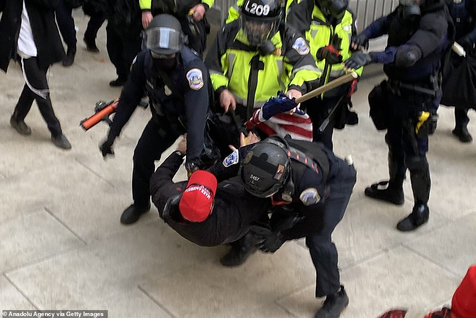A man wearing a Trump hat is wrestled to the ground by security forces after the unprecedented Capitol security breach