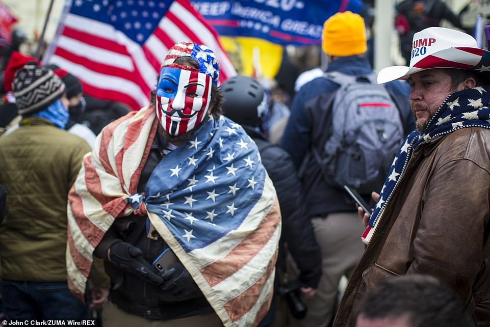 A Trump supporter wears a painted American flag Guy Fawkes mask amid chaotic scenes at the Capitol