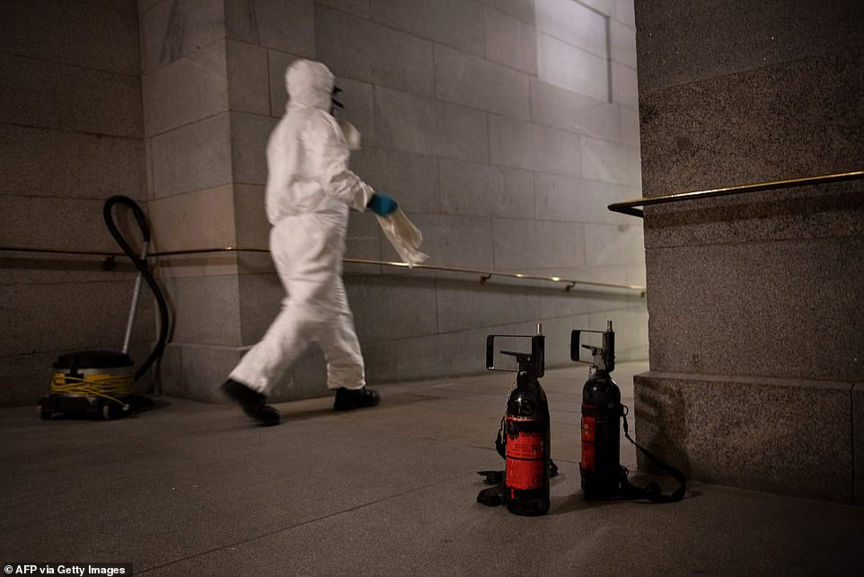 A worker walks past used crowd control chemicals near Capitol Police checkpoint