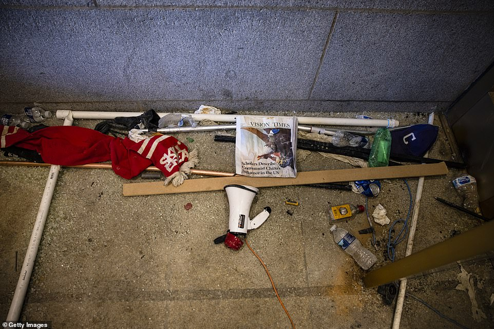 Damage and debris are seen left behind by a pro-Trump mob in the entrance to the western promenade, including a megaphone, liquor bottles and a Vision Times newspaper