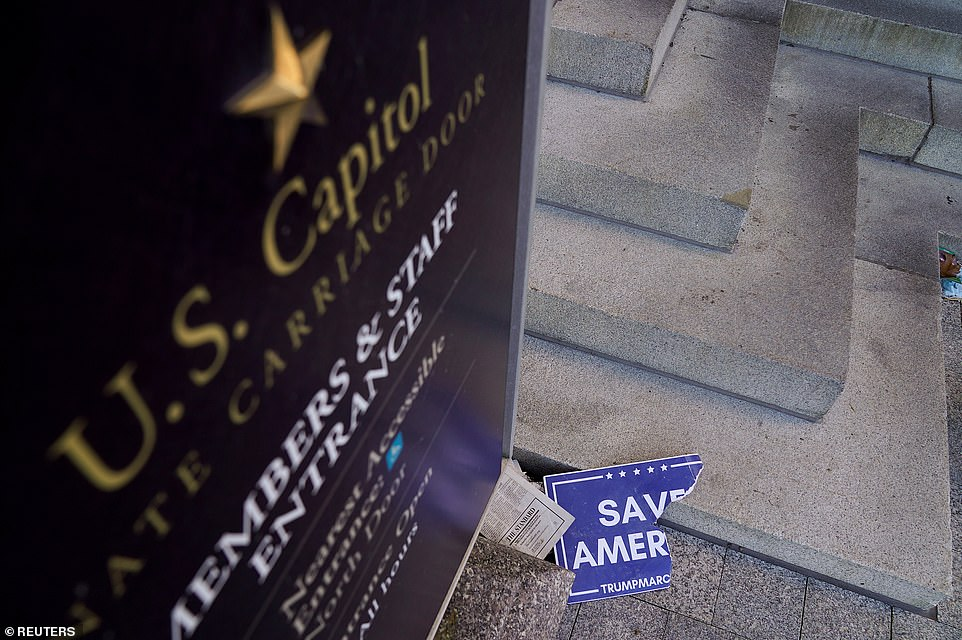 Scraps of a demonstrator's poster lays below a Congressional members and staff entrance sign