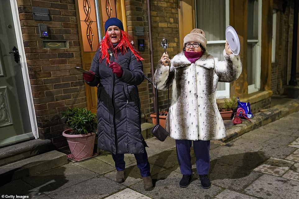 A mother and daughter stand outside their home in Saltburn-by-the-Sea and take part in the new Clap for Heroes event