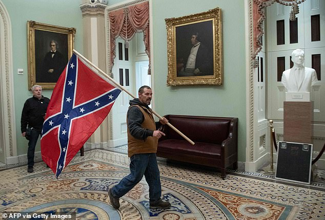 The Fox host also claimed that the group was not racist. Pictured above, a supporter in the US Capitol Rotunda on Wednesday afternoon holding a Confederate flag