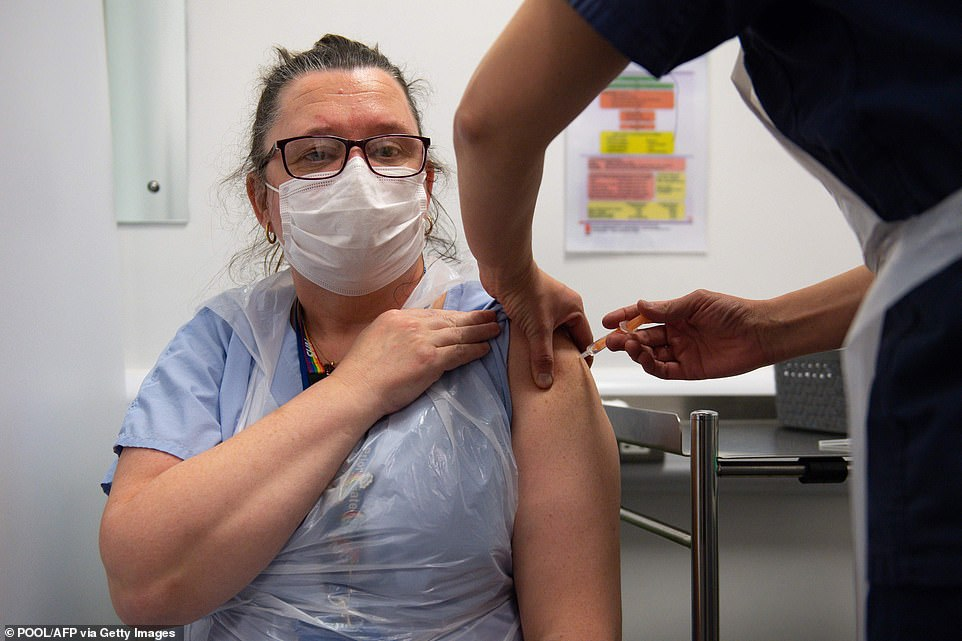 Professor Michael Parker suggested it should be made mandatory for frontline NHS staff to get the jab. Above is nurse Sue Toye, 51, being vaccinated at Coventry Health Centre yesterday