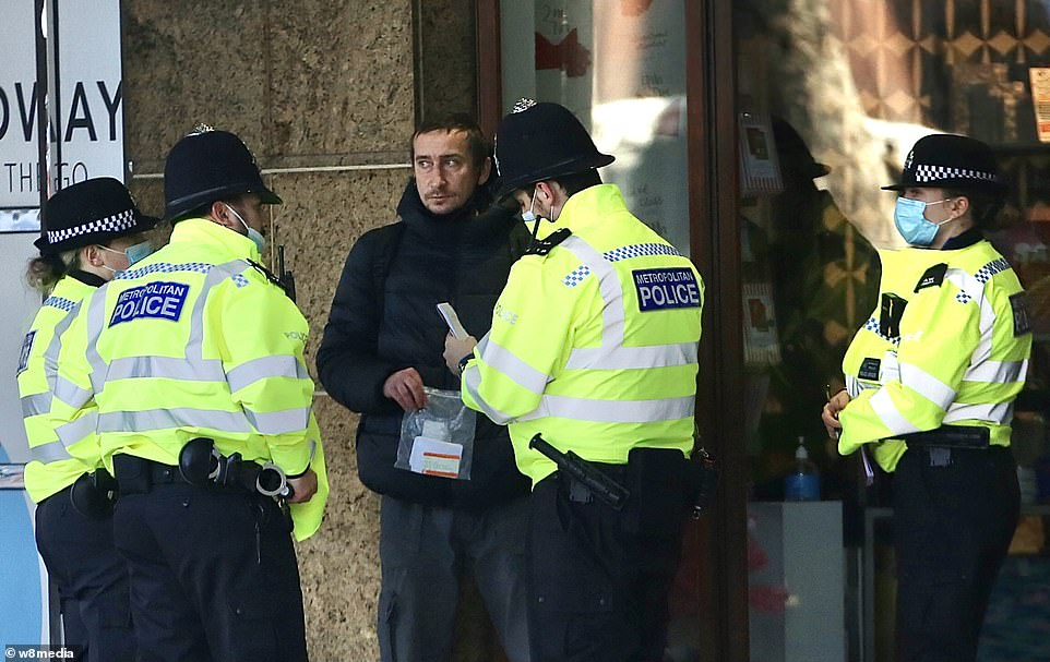 Five police officers surround a man atHammersmith Tube Station in west London yesterday as part of a crackdown on people shunning lockdown