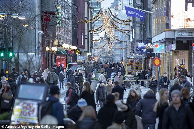 The new law, which comes into force on Sunday, will enable the government to close businesses, shopping malls or public transport as well as set limits on the number of people at gatherings. Pictured: Shoppers in Stockholm, Sweden on December 23