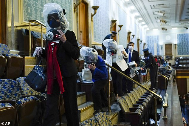 People wearing gas masks take shelter in the House gallery as protesters try to break into America's lower chamber
