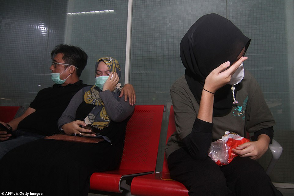 Terrified relatives of the 62 people onboard the missing Sriwijaya Air flight wait for news at the Supadio airport in Pontianak - where the plane was expected to land