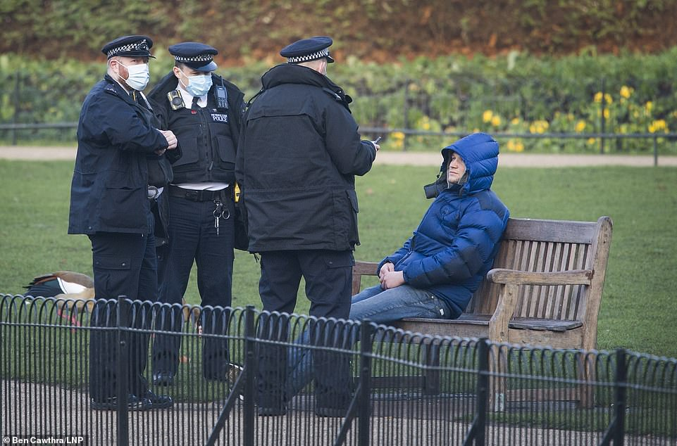 Three police officers wearing face masks question a man sitting on a bench in St James's Park in central London this morning
