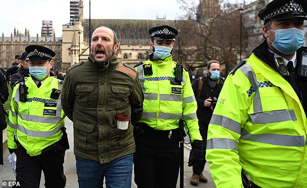 Police blasted a 'small selfish minority' ignoring the rules and promised to come down hard on transgressors who are refusing to stop partying despite the highly transmissible pathogen being rife. Pictured: A man is arrested by police during an anti-lockdown protest at Parliament Square in London on 6 January