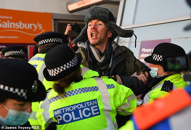 Police confronted protesters chanting 'take your freedom back' as they marched through Clapham on Saturday to call for opposition against national lockdown measures ordering people to stay at home