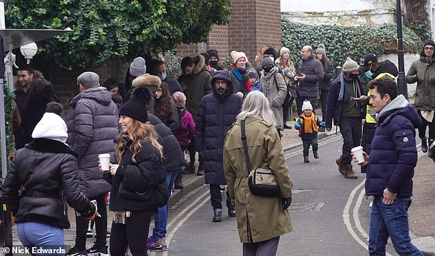 Pictured: People queue for pancakes in Hampstead, North London today despite London Mayor Sadiq Khan declaring a state of emergency in the capital due to a rapid rise in cases