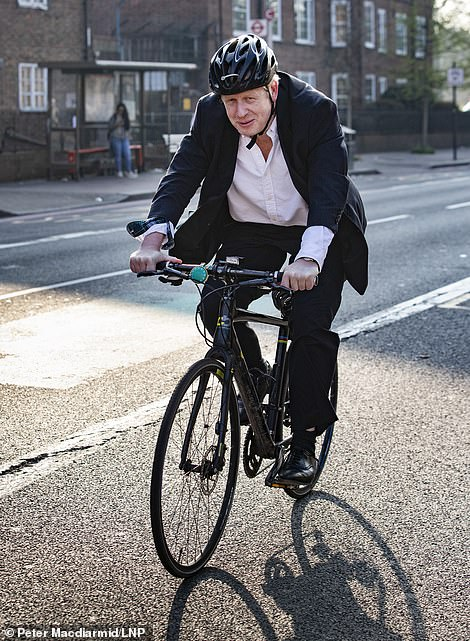 A file picture of Mr Johnson cycling in London
