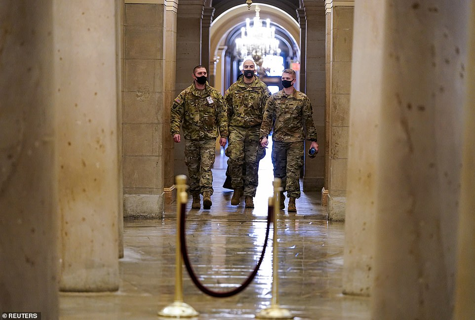 An FBI bulletin obtained by ABC News on Monday raised alarm about a group which is calling for the 'storming' of state, local, and federal government administrative buildings and courthouses should President Donald Trump be removed from office prior to Joe Biden's inauguration on January 20. Pictured: US National Guard members walkamong the columns of the crypt beneath the Capitol rotunda on Monday morning
