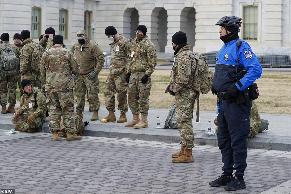 A Capitol Police officer stands alongside members of the New York National Guard on Monday morning