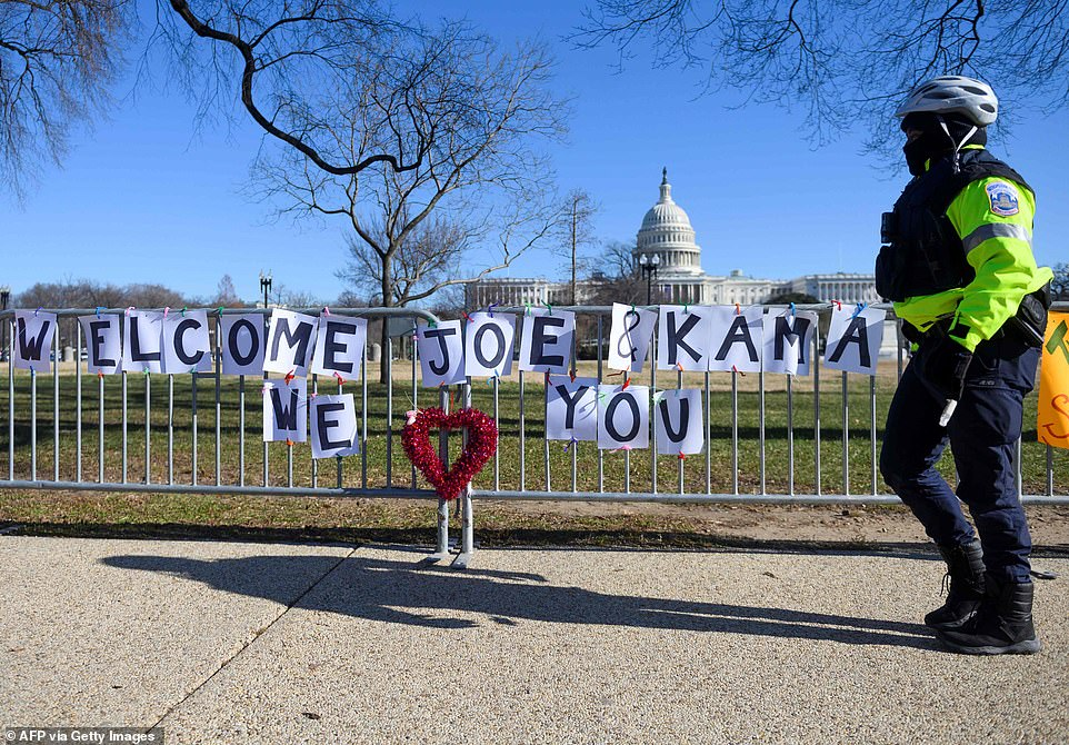 A police officer passes signs of support for Biden and Harris near the US Capitol in Washington, DC, on Sunday