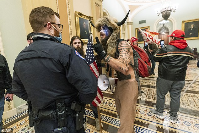 Chansleywearing a fur hat with horns was spotted speaking to a Capitol police officer