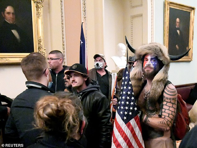Chansley stands with other Trump supporters as they demonstrate on the second floor of the U.S. Capitol near the entrance to the Senate after breaching security defenses