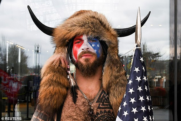 Chansley poses with his face painted in the colors of the U.S. flag as supporters of U.S. President Donald Trump gather in Washington before the protest