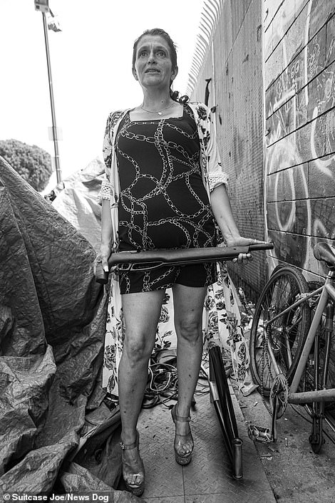 Chelsea, in high heels holding a huge pellet gun. She bought it to defend her tent - from rats. Typhus is an issue on Skid Row, that is carried by the fleas that live on the unwanted rodents