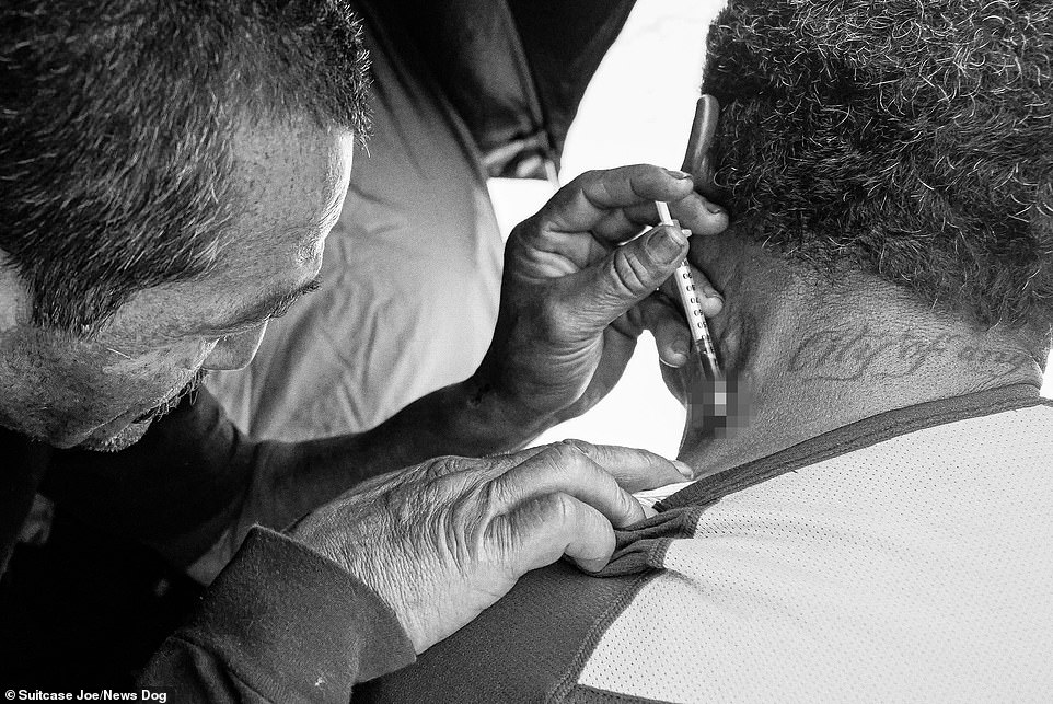 Pictured:A needle being injected into the neck of one of the residents in Skid Row.Some of the images are challenging, depicting the drug use and poverty rife in Skid Row that is unimaginable to many people