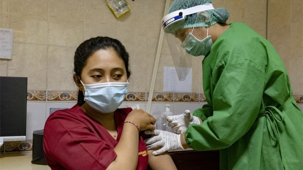 A woman receives a vaccine in Indonesia