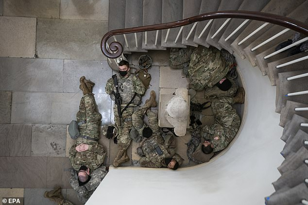 National Guard members get some shut eye on the floor of the Capitol as they cradled their weapons and huddled together