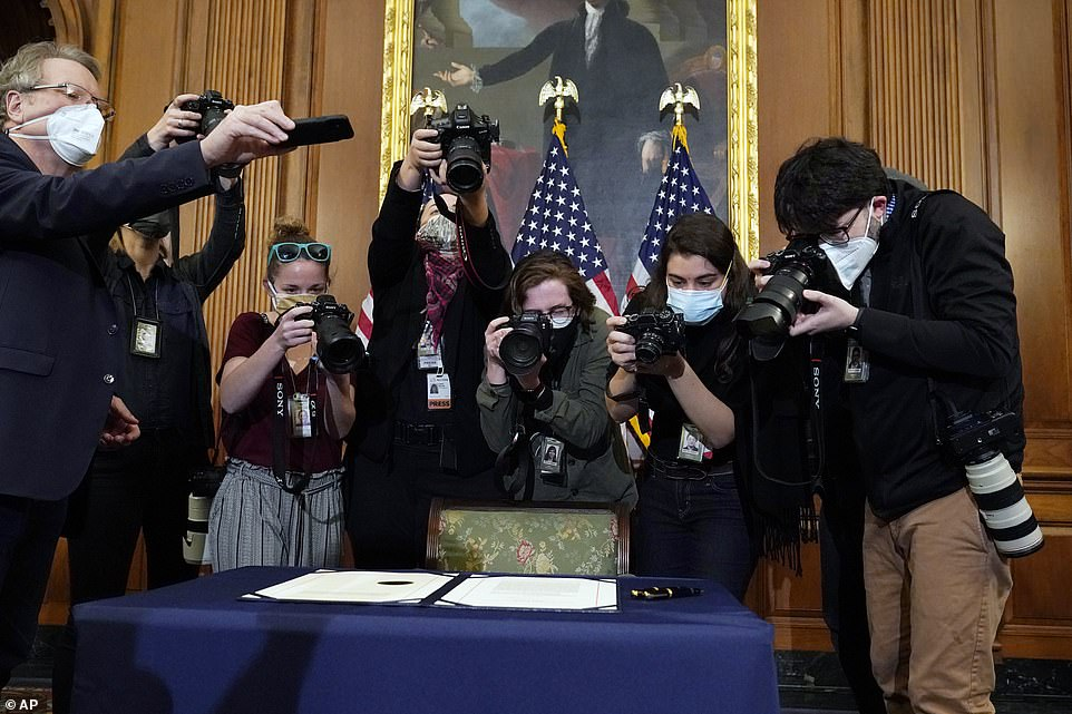 Photographers lean over the article of impeachment Wednesday on Capitol Hill trying to get a good shot before an engrossment ceremony with House Speaker Nancy Pelosi