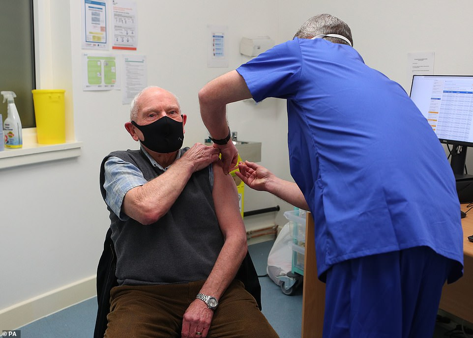 Pharmacist Andrew Hudson administers a dose of the coronavirus vaccine to Robert Salt, 82, at Andrews Pharmacy in Macclesfield, Cheshire.