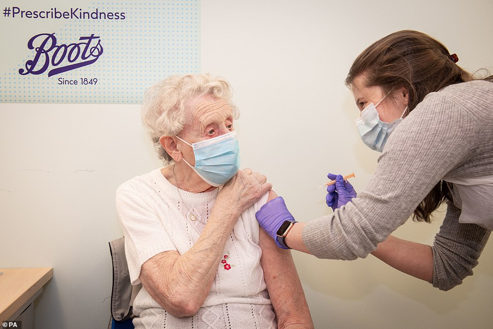 Brenda Clegg, 92, receiving a dose of the Covid-19 vaccine from pharmacist Rae Hynes at the Boots pharmacy in Halifax, West Yorkshire