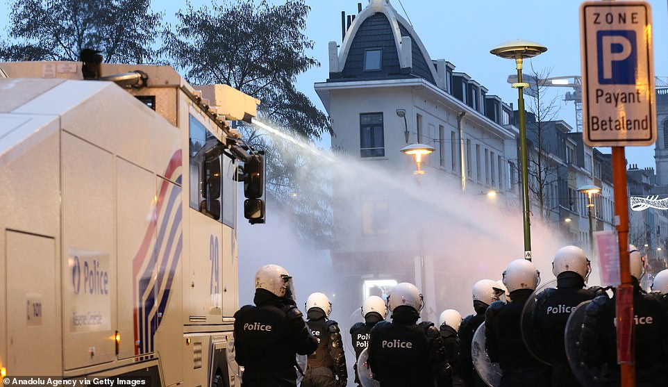 Police officers advance down a street in Brussels as a water cannon is uses to subdue protesters demonstrating following the death of 23-year-old Ibrahima Barrie