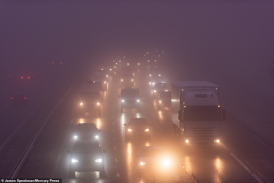 Vehicles queue on the M61 southbound near Bolton in Greater Manchester this morning after a collision in the freezing fog