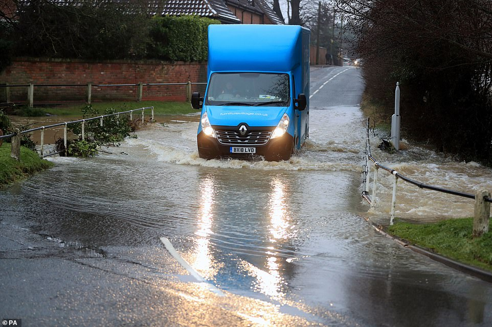 A van on a flooded road in Bottesford, Leicestershire, this morning as nearly 200 areas of the UK remain on flood watch