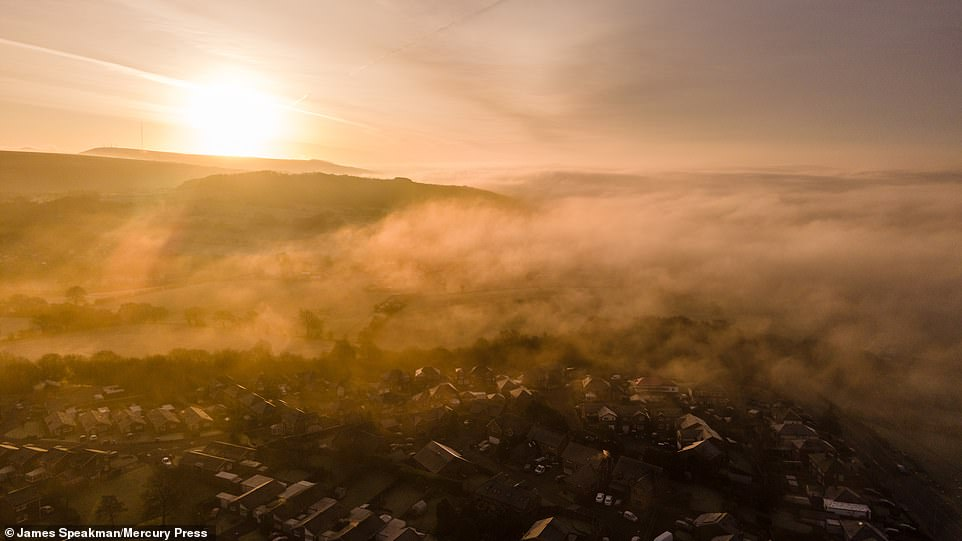 A beautiful misty sunrise behind Winter Hill and over low lying fog near Chorley in Lancashire this morning