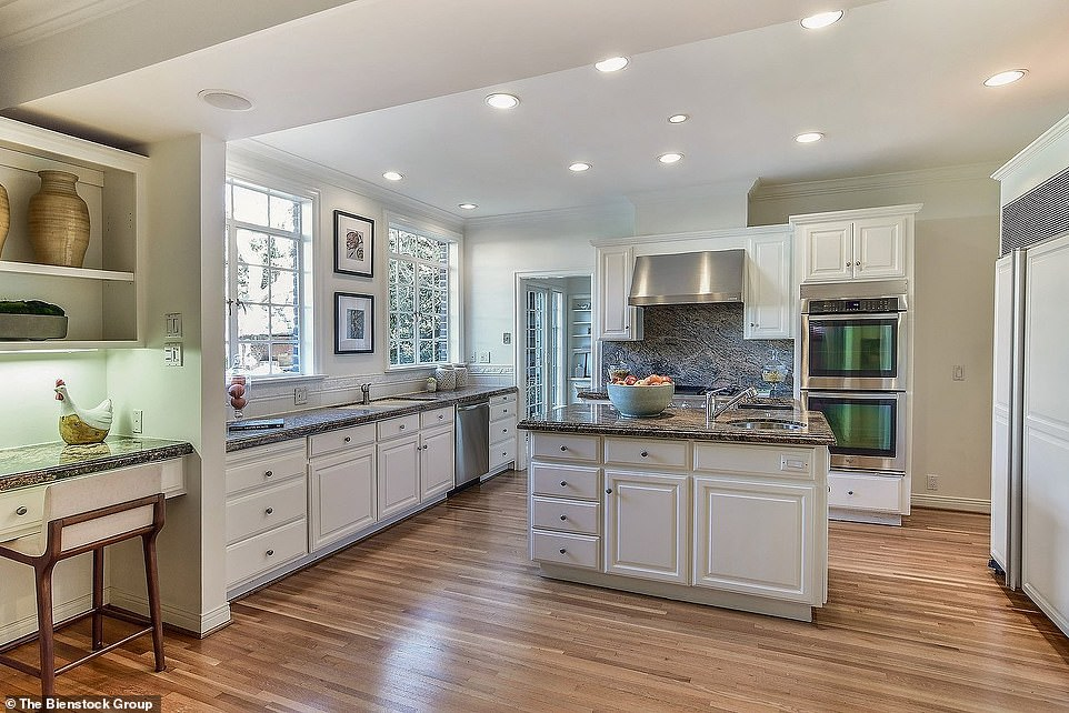 Let's cook! The kitchen looks recently remodeled with white cabinets, dark gray quartz counters, French windows, an island with a sink and faucet, and wood floors